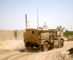 Military-Tank-Driving-Down-Dusty-Road-in-Desert